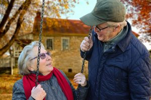 An older adult couple is pictured in front of a house, the woman sits on a swing