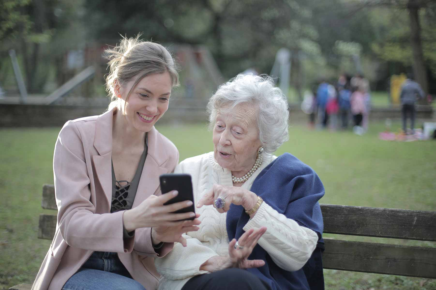 A young woman and an older adult woman sit together on a bench looking at a phone
