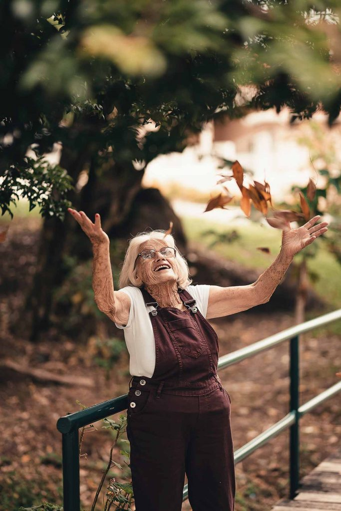 An older adult woman throws fall leaves into the air