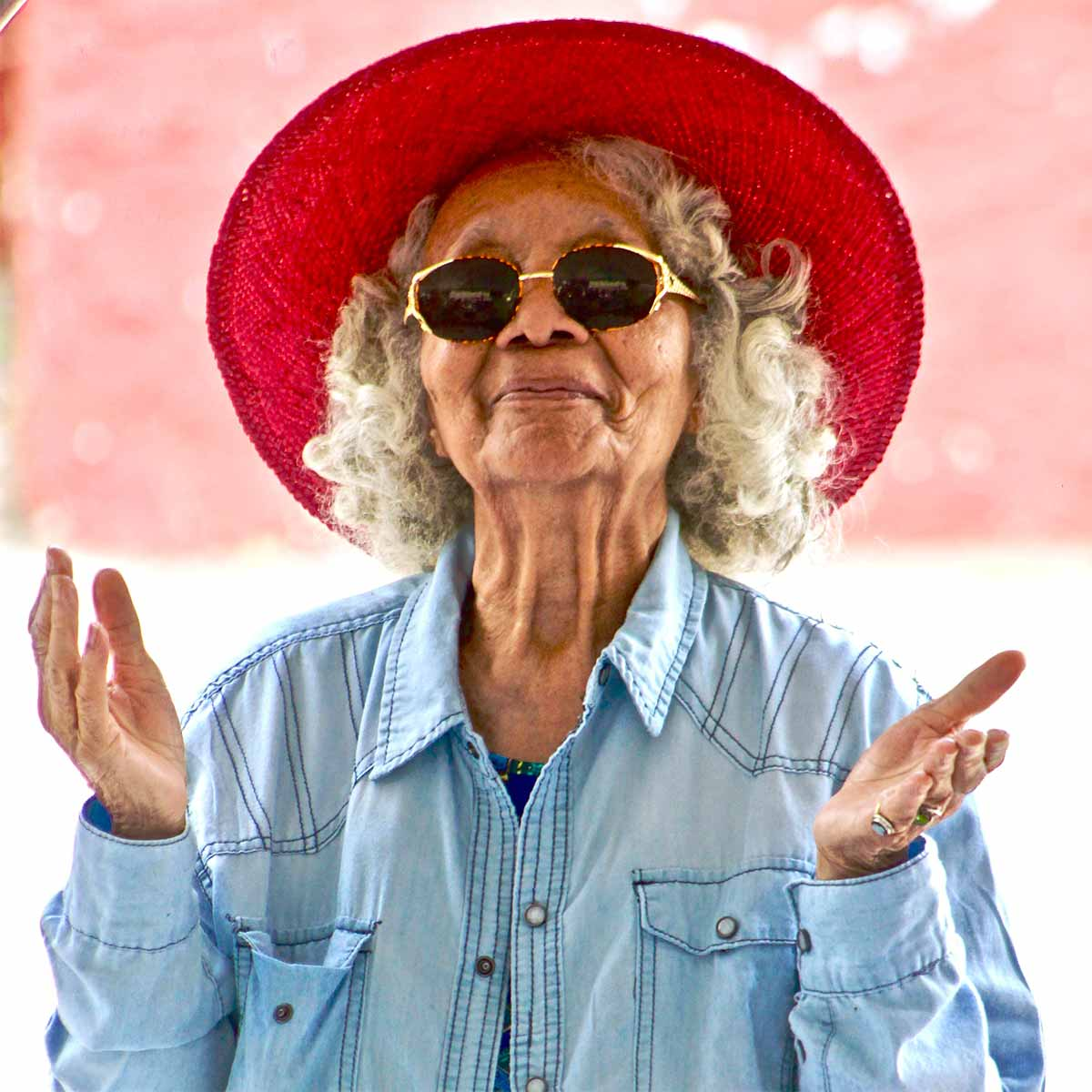 An older adult woman with a bright red hat and sunglasses is smiling