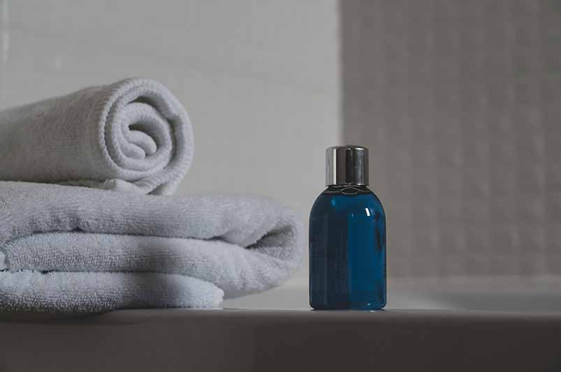 A folded towel and bottle of soap are shown