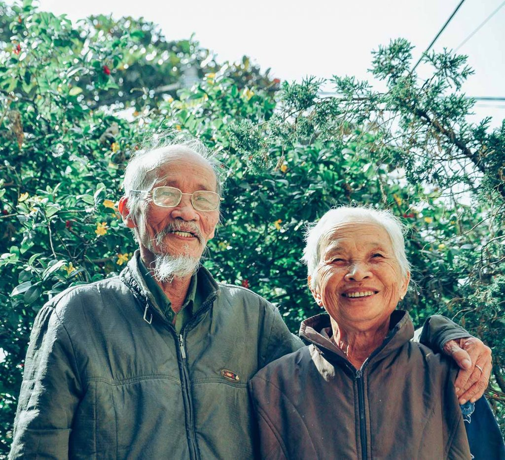 An older adult couple stands arm in arm in front of a tree, they are smiling