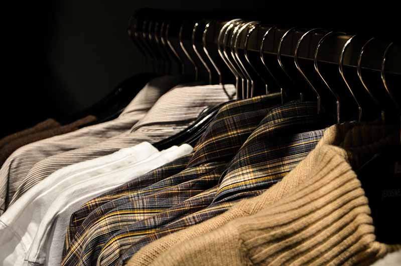 A closet with men's shirts hanging on the rack