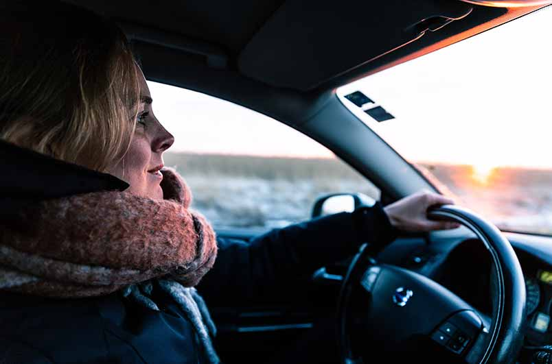 A woman drives a car, she is wearing a scarf and smiling