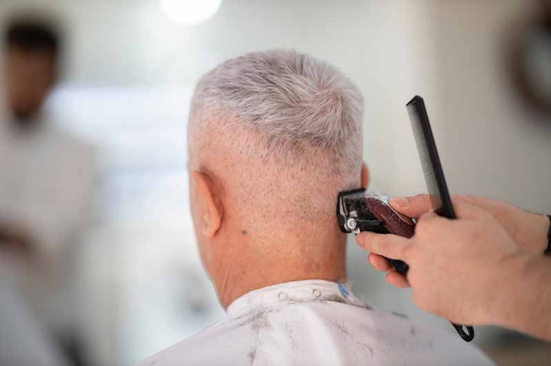 An older adult man gets his hair cut