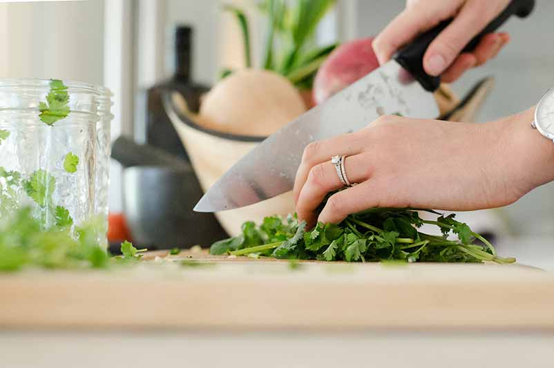 A woman's hands are shown as she chops cilantro