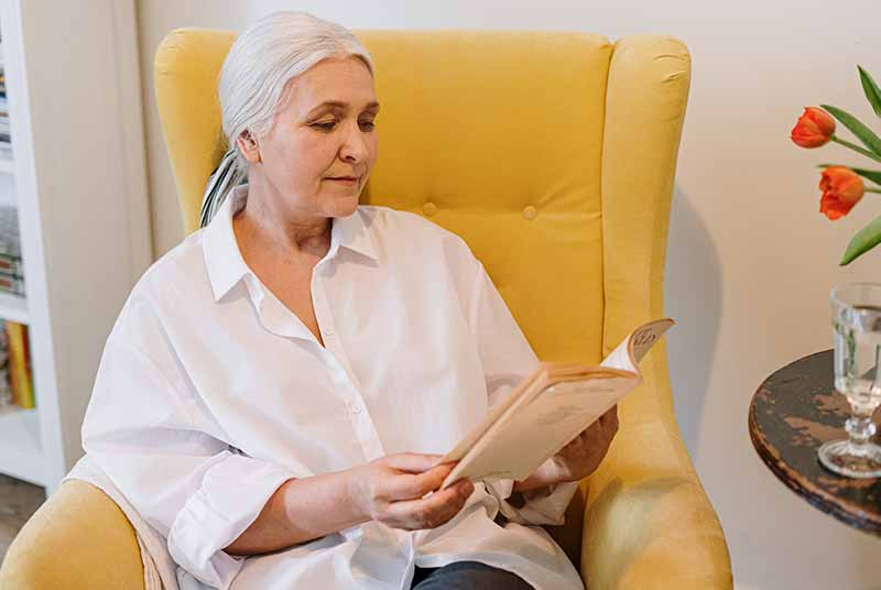 An older adult woman sits in a yellow chair and reads a book, she is wearing a white shirt